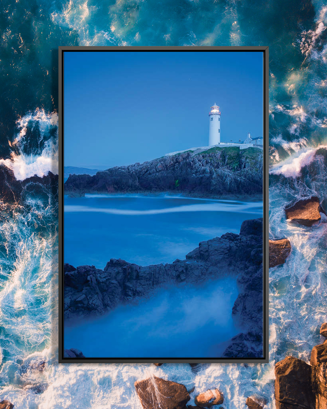"""Dusk I, Fanad Head Lighthouse, County Donegal, Ulster Province, Republic Of Ireland"" by Gareth McCormack shows a blue sea surrounded by bank rocks under a blue sky with a lighthouse in the distance."