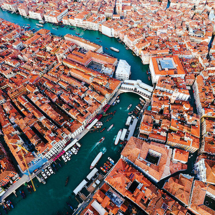 """""""Grand Canal Aerial, Venice II"""" by Matteo Colombo shows an overhead view of buildings with orange rooftops surrounding a blue canal with boats in it."""