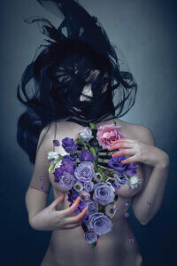 """""""Broken Heart"""" by Natalie Shau shows a nude woman with black hair flowing over her face while she grips flowers emerging from her chest."""