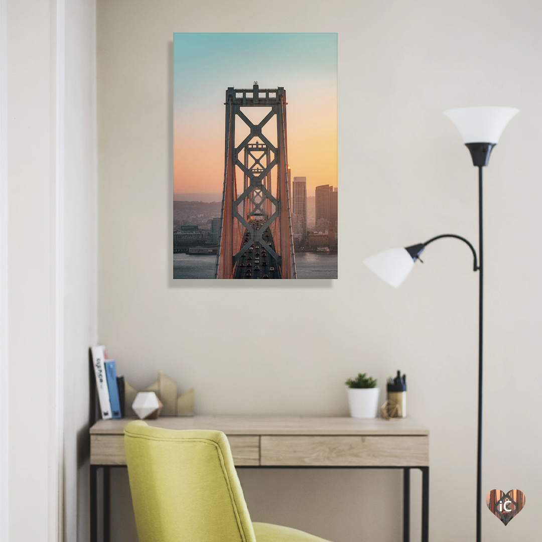 """""""Bay Bridge San Fran"""" by Peter Yan shows the San Francisco Oakland Bay Bridge against an ombre blue and yellow sky with buildings in the distance."""