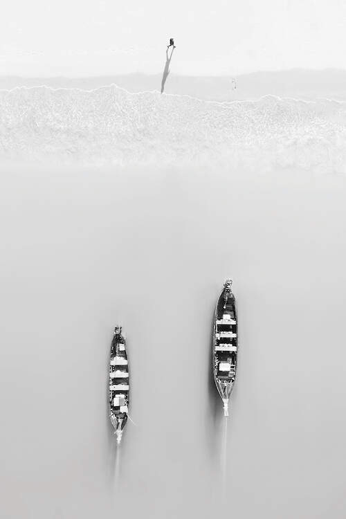 """""""Morning Exercises"""" by Zhou Chengzhou shows a person walking on a beach as two boats in the water approach the shore."""