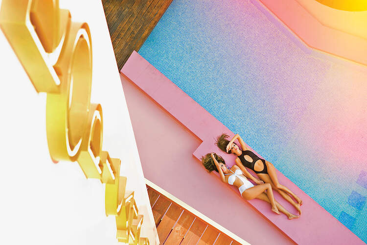 """""""Tropicana Girls"""" by Jordi Gomez shows two girls in bathing suits laying poolside on a pink floor with a flare of peeking over them."""