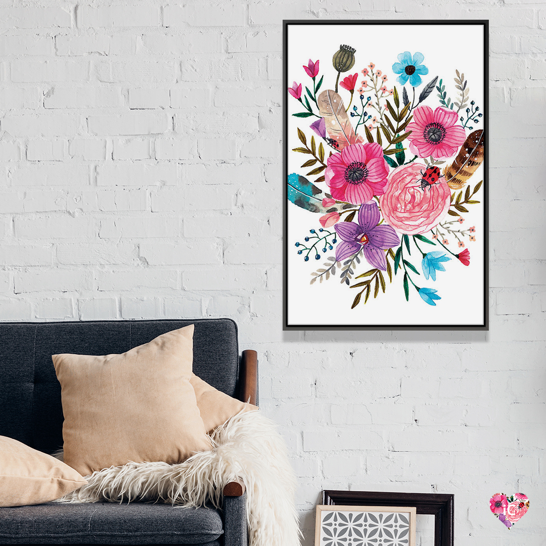 Watercolor illustration of pink, purple, and blue flowers and multi-color leaves framed on a white brick wall in a living room with a gray couch and beige throw pillows