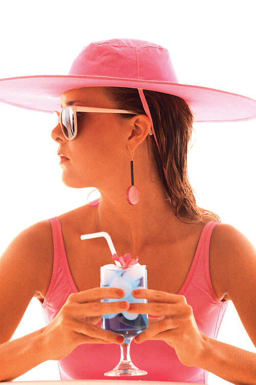 """""""1980s Young Woman In Bathing Suit Having A Drink"""" by Vintage Images shows the profile of a woman wearing a pink hat, pink bathing suit, and sunglasses while holding a drink."""