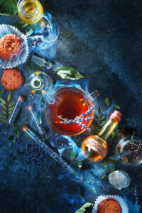 """""""No Worries Mixture"""" by Dina Belenko shows glasses and potion bottles filled with liquids surrounded by tubes of blue seeds and cookies."""