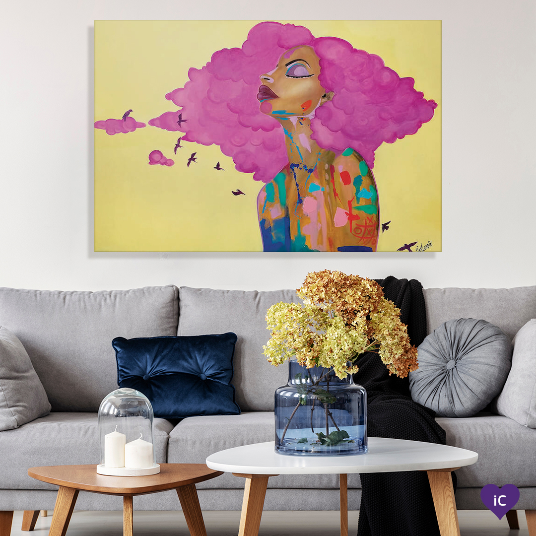 Painting of the profile of a black woman with pink hair and splashes of paint on her body with small pink birds flying around her against a yellow background, on a wall over a living room couch