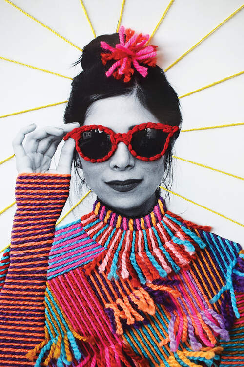 """Fashion"" by Victoria Villasana shows a woman wearing red sunglasses and a high-neck, multicolored top all made out of yarn."