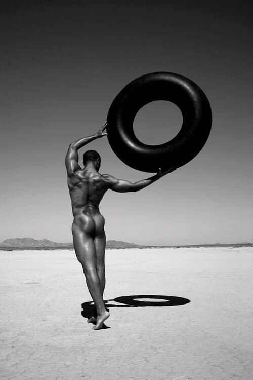 """""""Ramel With Tire"""" by Gregory Prescott shows a black and white photo of a black man walking through a desert holding a large black tire"""
