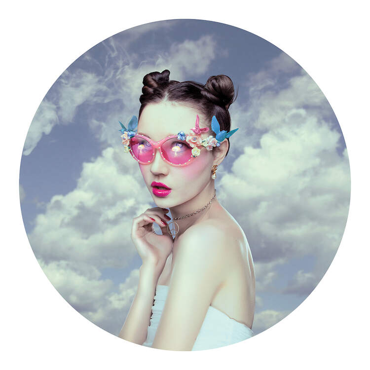 """""""Oblivion"""" by Natalie Shau shows a woman wearing space buns and pink sunglasses decorated with birds and flowers with clouds in the background."""
