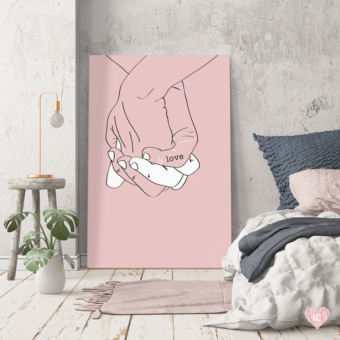 "Graphic of two held hands with the word ""love"" written on them against a pink background leaned on a wall in a neutral colored bedroom"