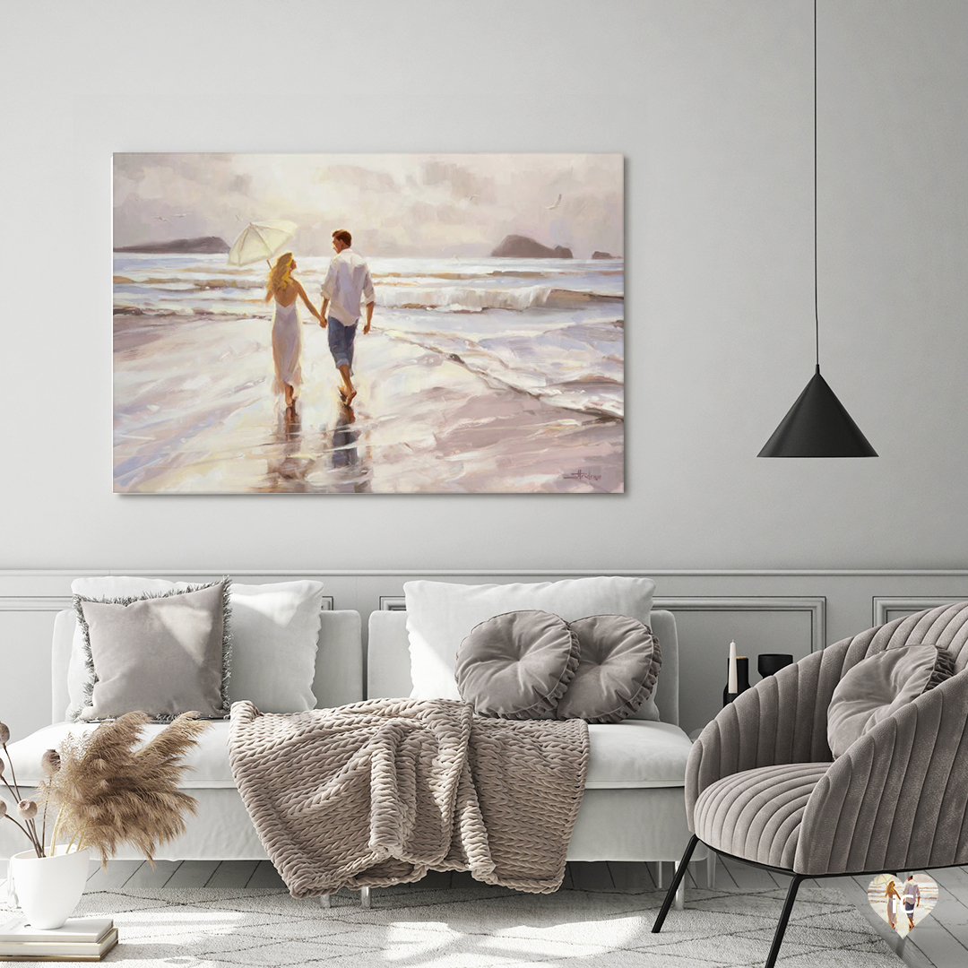 Man and woman holding hands walking on a beach hanging on a white wall in a neutral colored living room