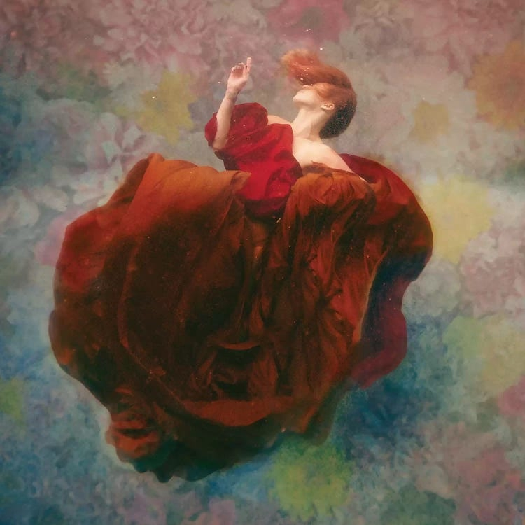 Bloom by Lola Mitchell showcases a woman with red hair wearing a red dress floating underwater