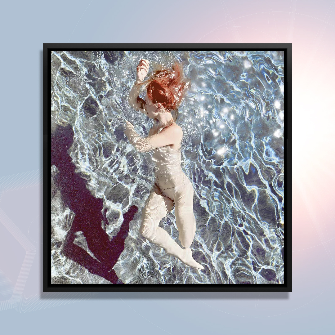 Floating II by Lola Mitchell showcases a woman with red hair wearing skin-colored undergarments while floating underwater