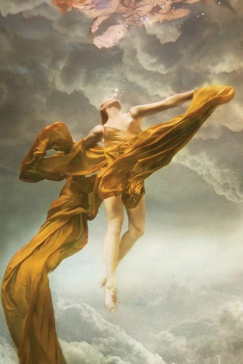 Heavens by Lola Mitchell showcases a woman floating underwater wearing a yellow dress with fabric flowing around her