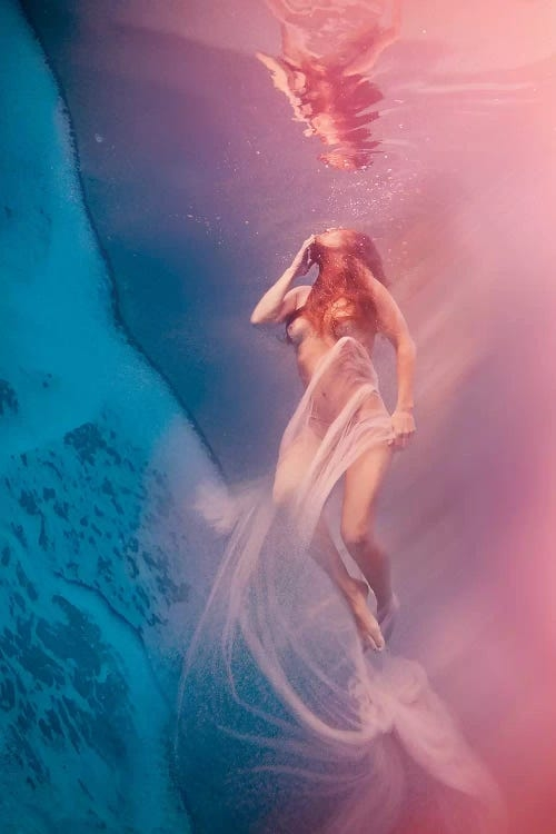 Surreal Dreams by Lola Mitchell showcases a nude woman floating under pink and blue water while wrapped in sheer fabric