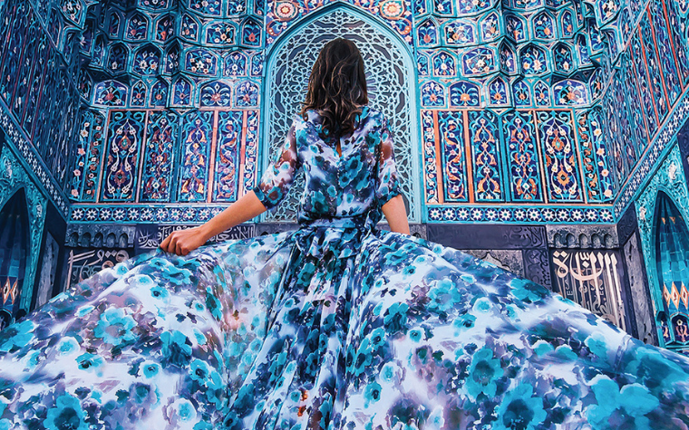 Photography of woman in blue dress looking up at blue cathedral by female artist Hobopeeba