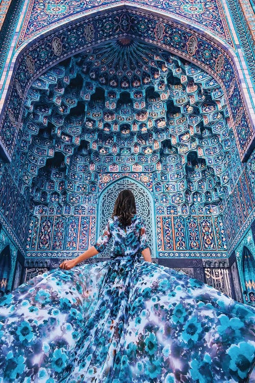Photograph of woman in blue dress looking up at blue cathedral by female artist Hobopeeba