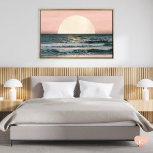 Framed wall art of a sunset over the ocean by Nature Magick above a gray bed