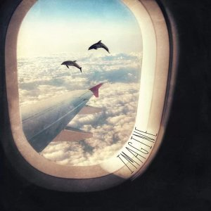 Wall art of the view from a plane window featuring dolphins swimming in a cloudy sky