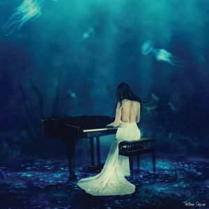 Art trend 2021 wall art of a woman in a white dress playing piano in the ocean