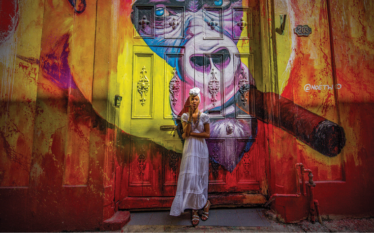 Authenticity photograph of a woman smoking in front of a colorful mural of an ape smoking in Havana